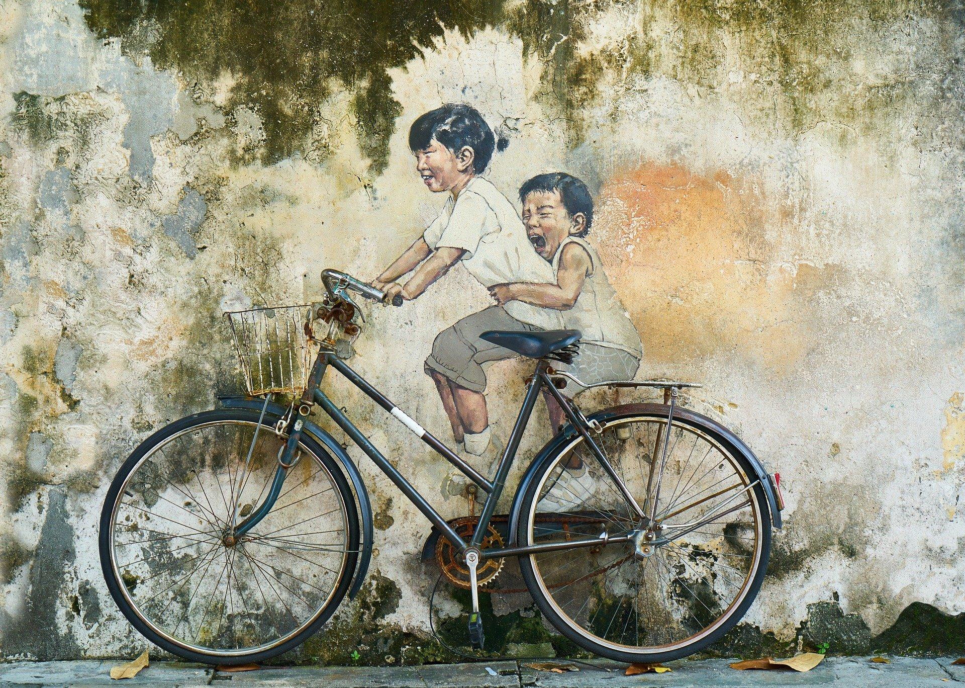 Mantenimiento Bicicleta antigua sucia y mal engrasada con dos niños pintados en la pared